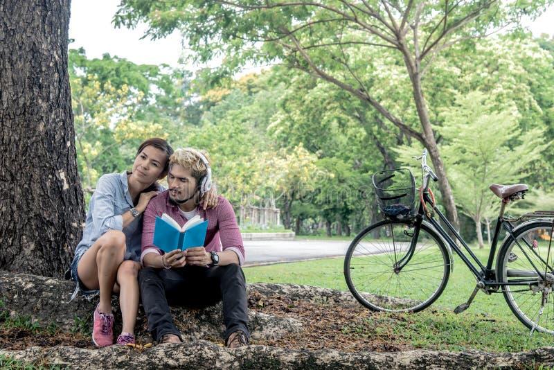 Couples heureux lisant un livre tandis que musique de écoute images libres de droits