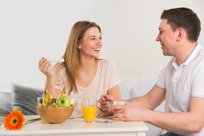 Couples heureux mangeant à la maison image stock