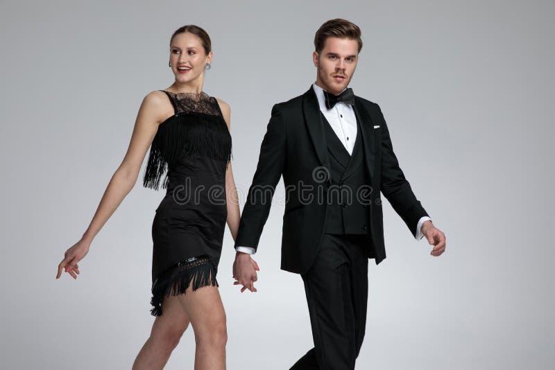 Couples heureux marchant au côté et tenant des mains photographie stock