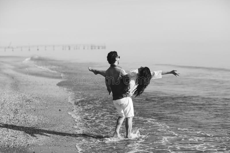 Couples heureux marchant et jouant sur la plage Un homme tourne la fille dans des ses bras Rebecca 36 images stock