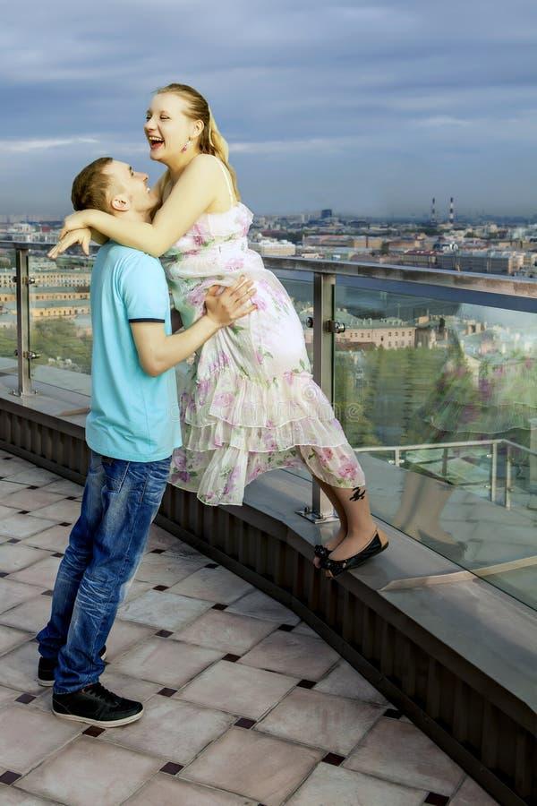 Couples heureux marchant sur le toit d'un haut bâtiment, avec des vues de la grande ville. Rire de fille, étreignant l'amant. images libres de droits