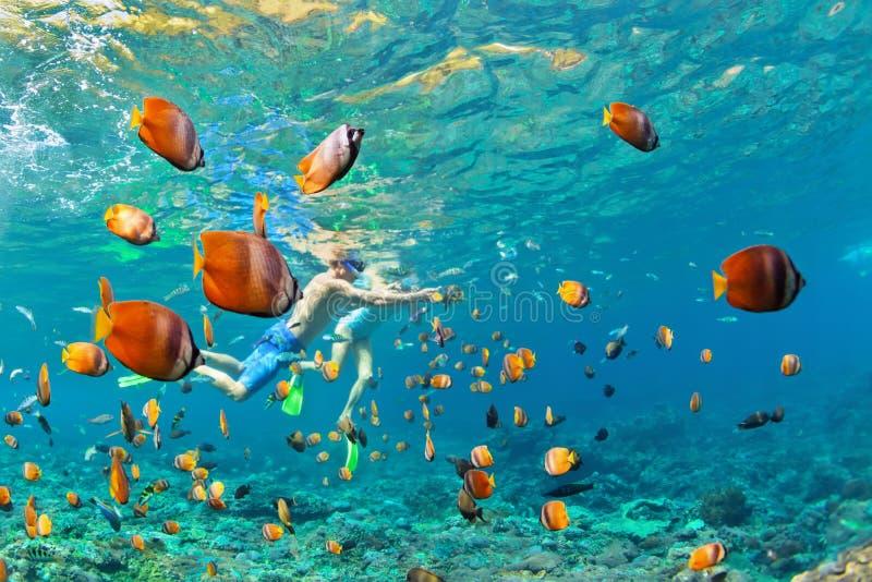 Couples heureux naviguant au schnorchel sous l'eau au-dessus du récif coralien photo libre de droits