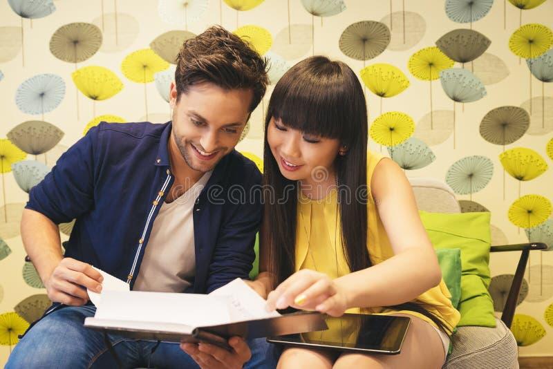 Couples heureux observant le media social dans un carnet à la barre photo libre de droits