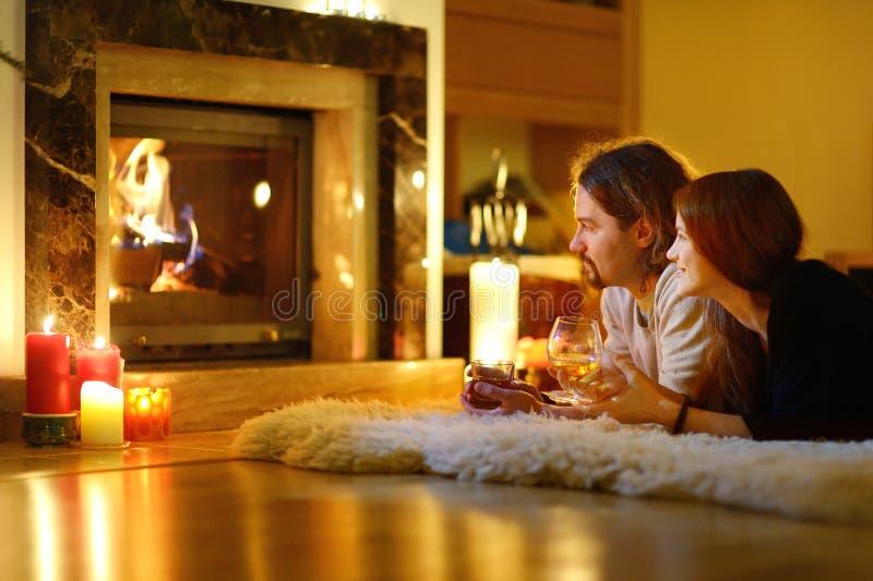 Couples heureux par une cheminée sur Noël photographie stock