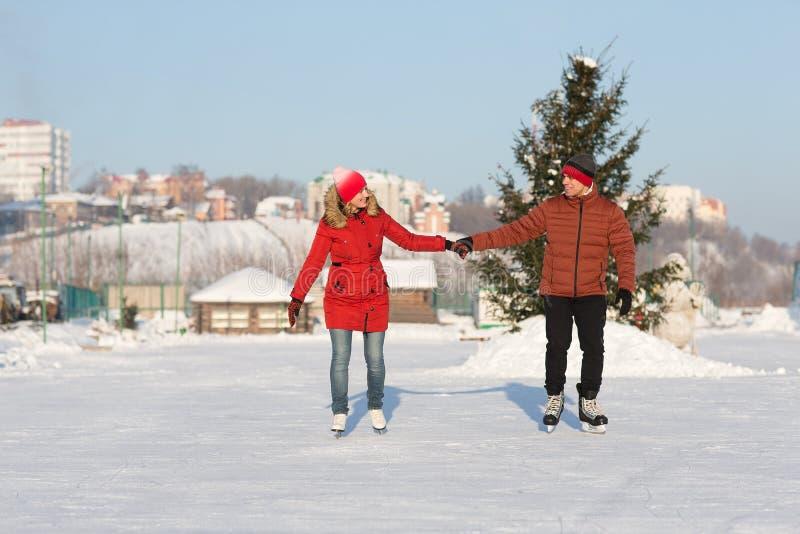 Couples heureux patinant à l'hiver de piste photo stock