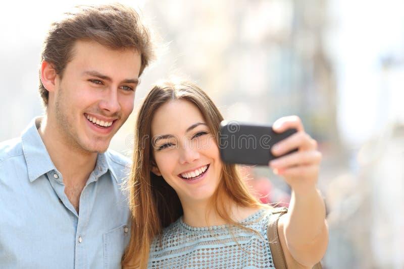 Couples heureux prenant des selfies utilisant le téléphone dans la rue photographie stock