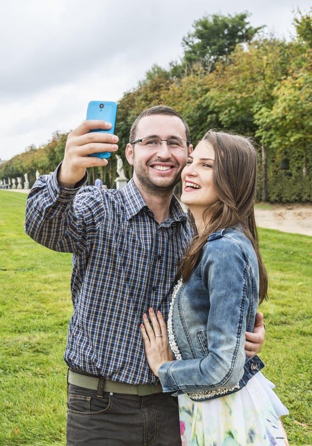 Couples heureux prenant un selfie dans un jardin français photographie stock libre de droits