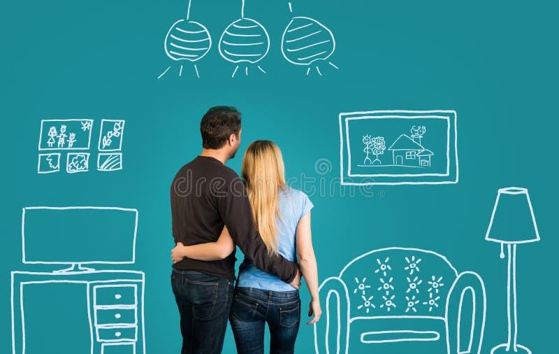 Couples heureux rêvant de leur nouvelle maison ou fournissant sur le fond bleu Famille avec le dessin de croquis de leur futur in images stock