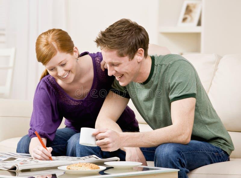 Couples heureux recherchant par les annonces classifiées photographie stock