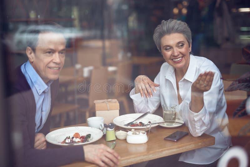 Couples heureux regardant sur le smth en dehors de du café photo stock