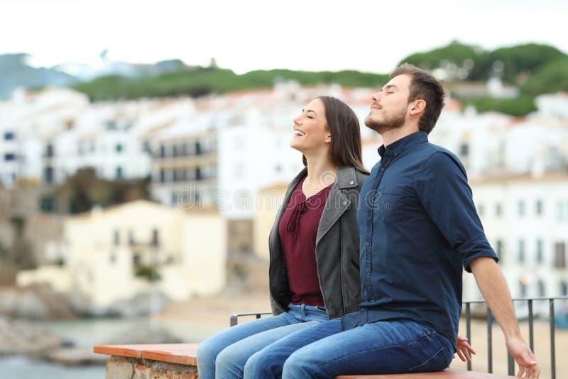 Couples heureux respirant sur un rebord des vacances image libre de droits
