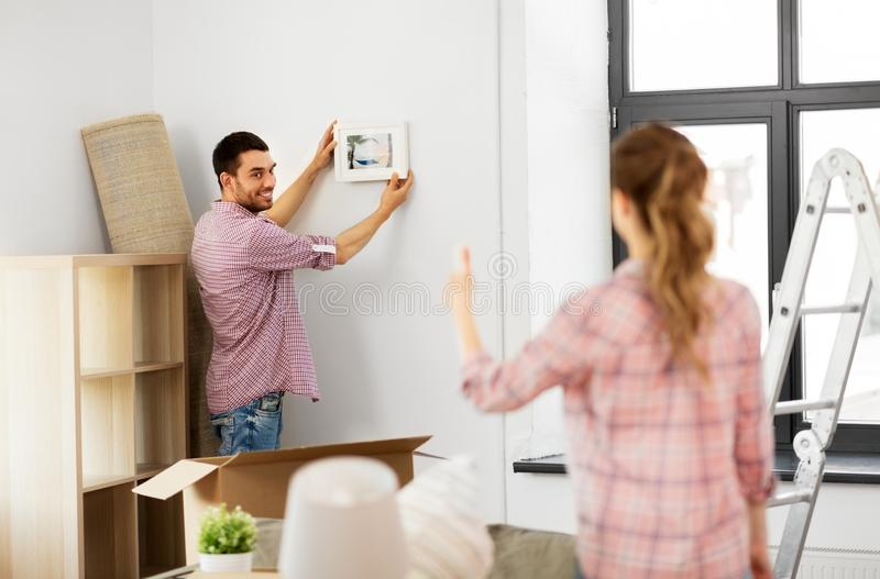 Couples heureux se déplaçant à la nouvelle maison et à la photo accrochante images libres de droits