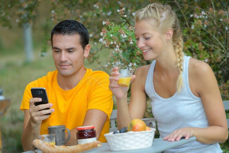 Couples heureux se reposant chez l'homme de café de rue à l'aide du téléphone photos stock