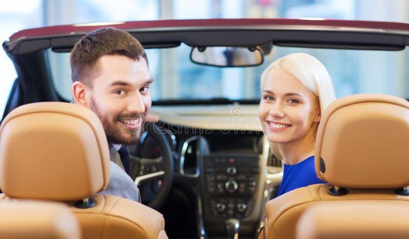 Couples heureux se reposant dans la voiture au salon de l'Auto ou au salon photographie stock