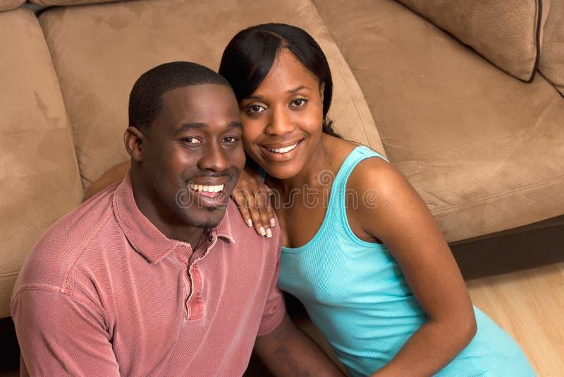 Couples heureux se reposant devant la fin de divan vers le haut image libre de droits