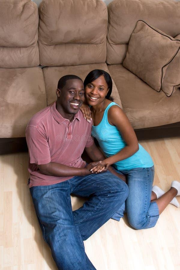 Couples heureux se reposant devant le divan - verticale images libres de droits