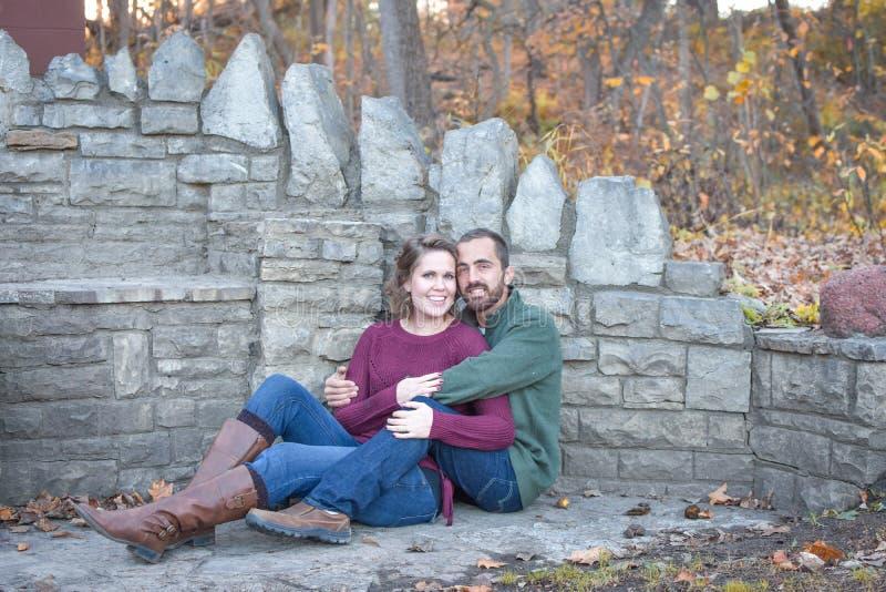 Couples heureux se reposant par le mur en pierre image stock