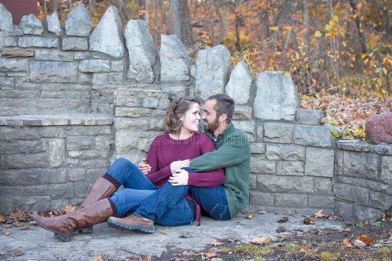 Couples heureux se reposant par le mur en pierre photographie stock