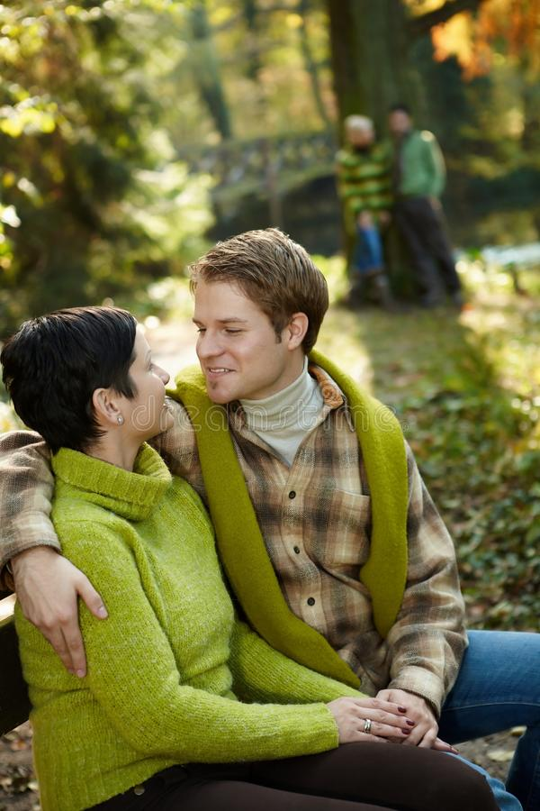 Couples heureux se reposant sur le banc de stationnement photographie stock