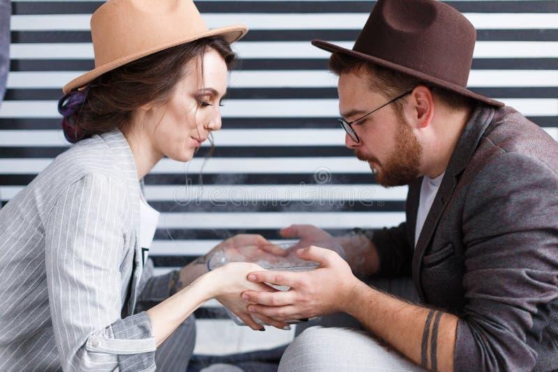 Couples heureux se reposant sur le plancher tenant le plat de tabagisme avec de la glace carbonique photographie stock