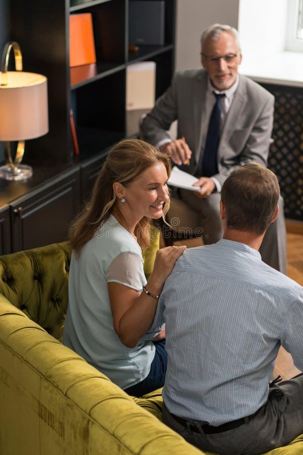 Couples heureux se reposant sur le sofa vert olive images stock