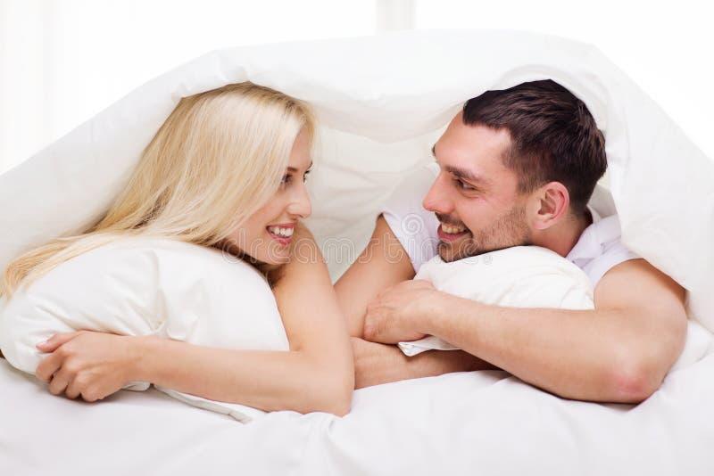 Couples heureux se situant dans le lit et parlant à la maison photos libres de droits