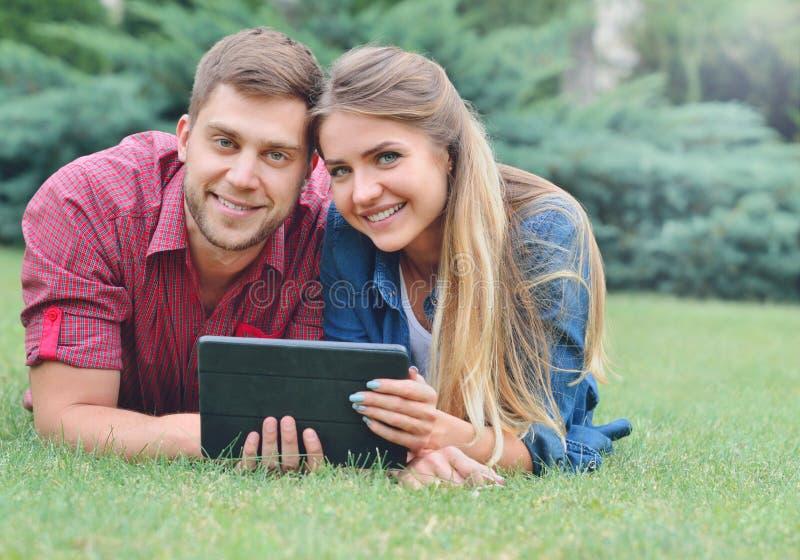 Couples heureux se situant en parc utilisant le PC de comprimé ensemble photographie stock libre de droits