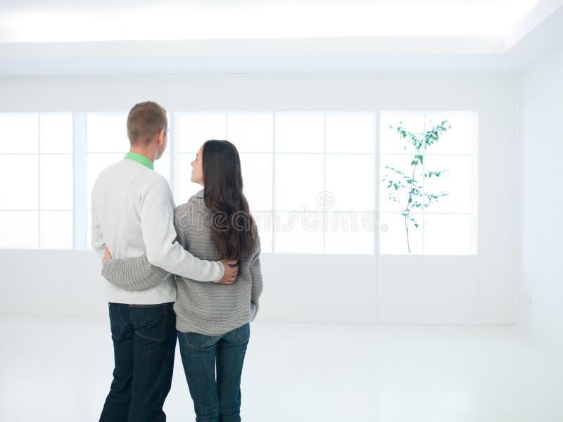 Couples heureux se tenant dans leur nouvelle maison images stock