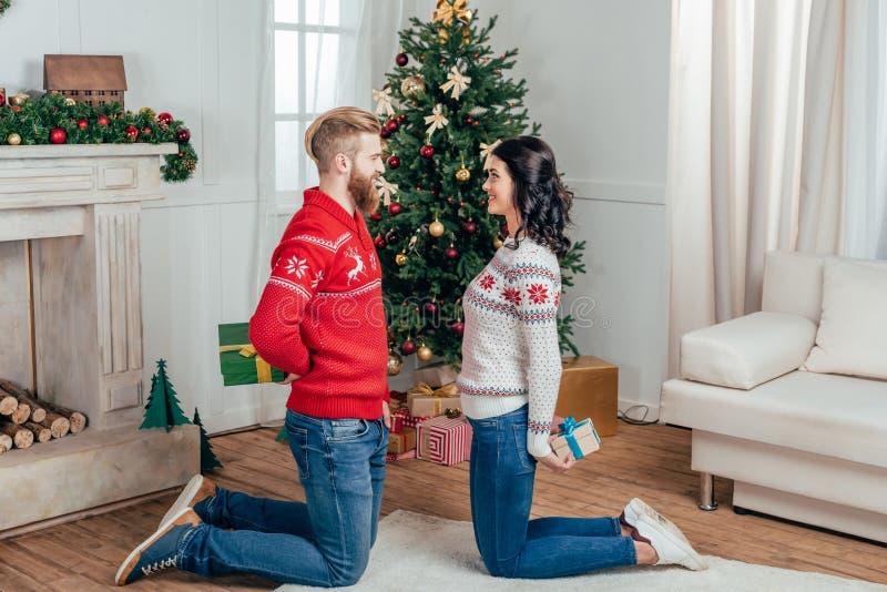 couples heureux se tenant sur des genoux avec des cadeaux dans Noël photos libres de droits
