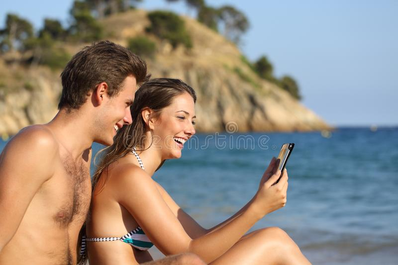Couples heureux sur la plage vérifiant le comprimé photographie stock