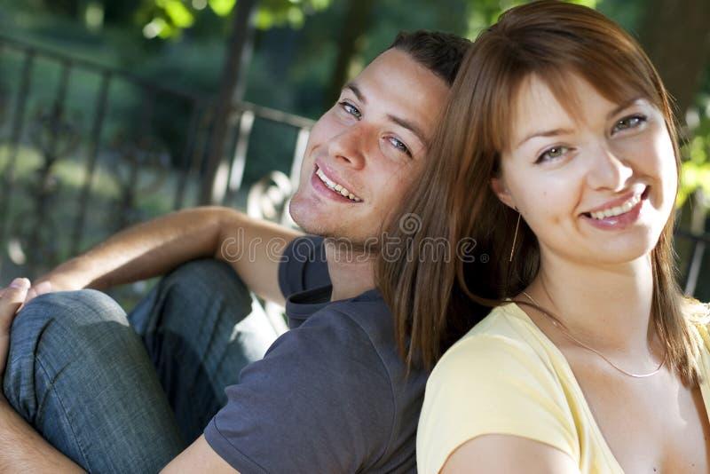 Couples heureux sur le banc en stationnement photographie stock libre de droits
