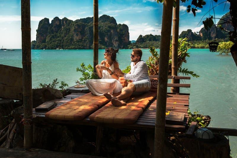 Couples heureux sur une île outre des jeunes couples de côte près de la mer Couplez les voyages autour du monde Couples dans l'am image stock