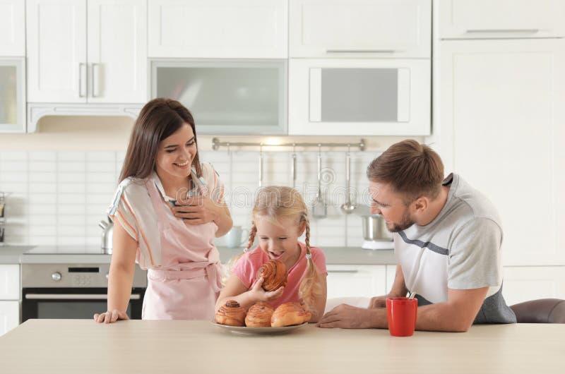 Couples heureux traitant leur fille avec fraîchement le petit pain cuit au four par four photo stock