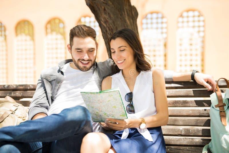Couples heureux utilisant la carte de ville pour la direction images stock