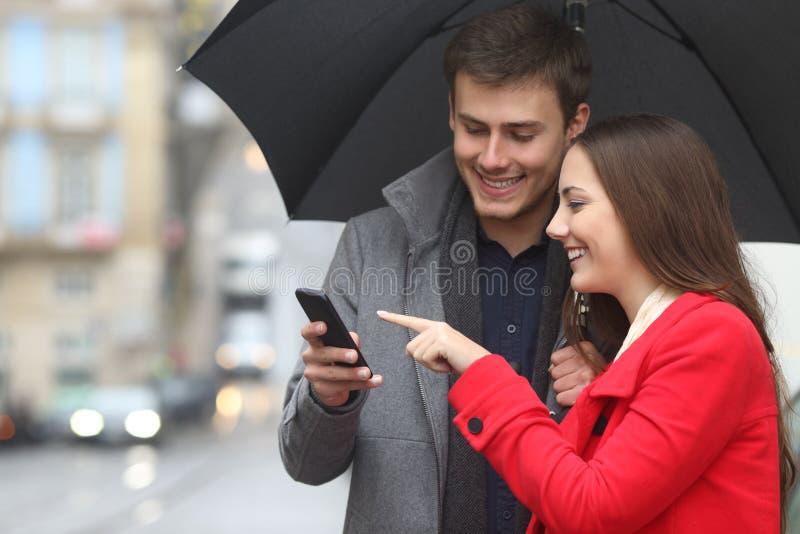 Couples heureux vérifiant le téléphone en hiver sous la pluie photographie stock libre de droits