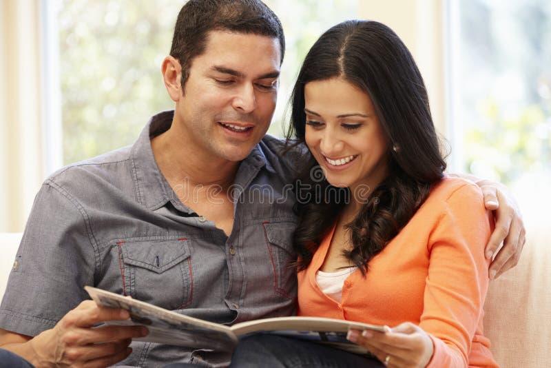 Couples hispaniques à la maison lisant le magazine images stock