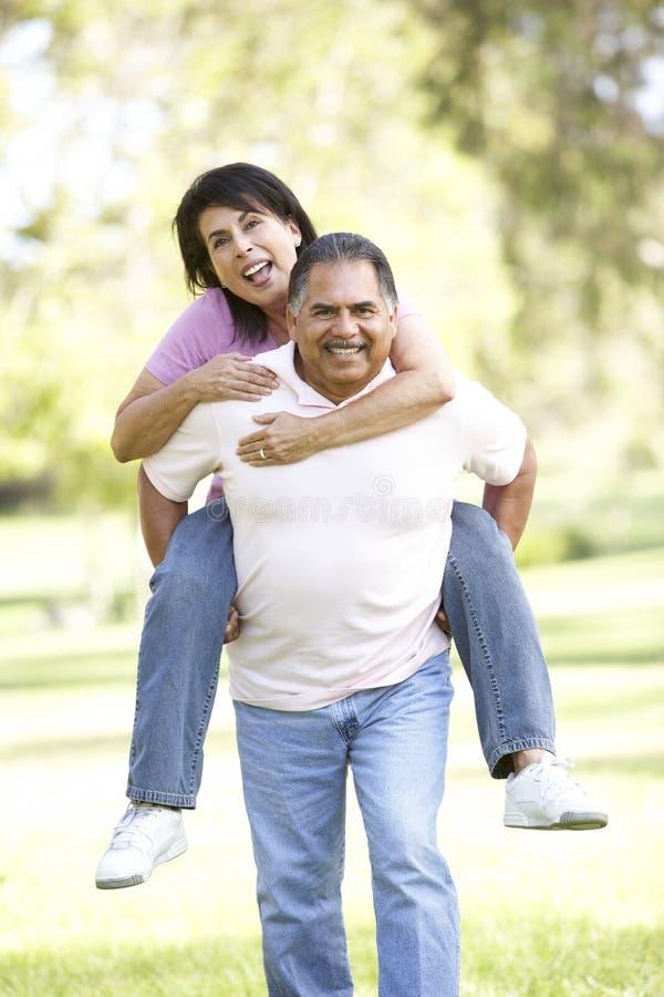 Couples hispaniques aînés ayant l'amusement dans le stationnement photo libre de droits