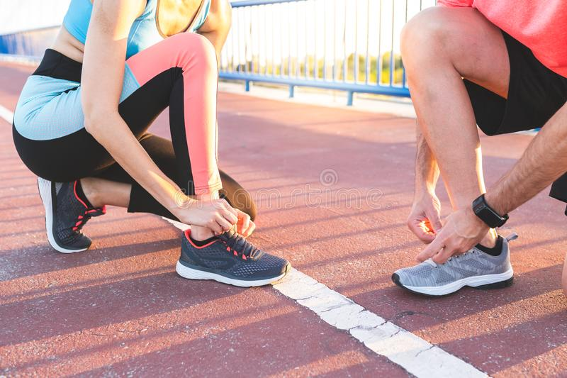 Couples hispaniques attachant leur entra?neur Shoes After Running ensemble dehors photo libre de droits