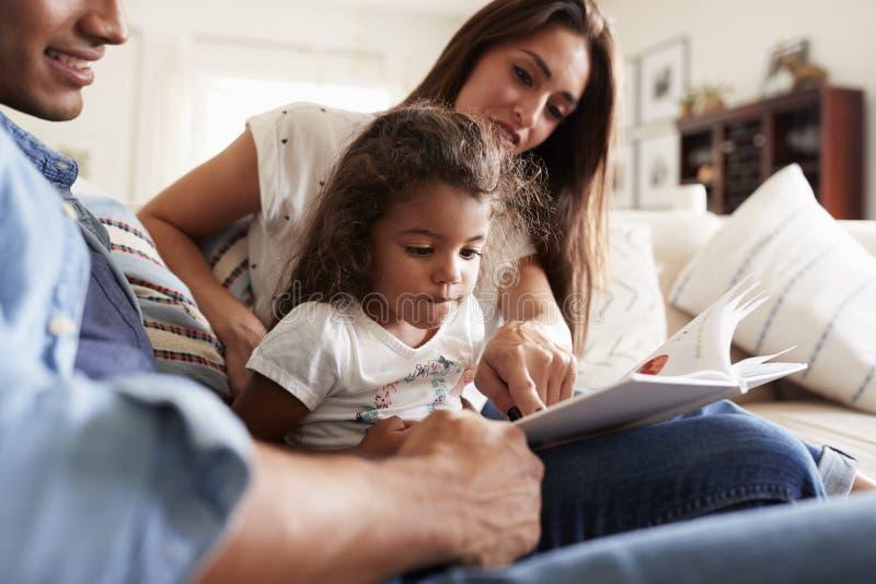 Couples hispaniques et leur jeune fille s'asseyant sur le sofa lisant un livre ensemble à la maison photographie stock libre de droits