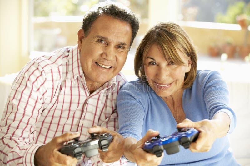 Couples hispaniques supérieurs jouant le jeu vidéo à la maison images libres de droits