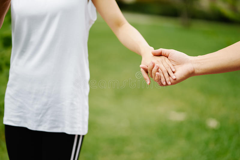 Couples holding hands in front of green grass stock photo