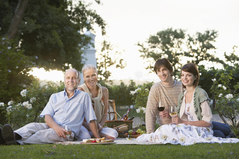 Couples Holding Wine Glasses On Picnic stock photography