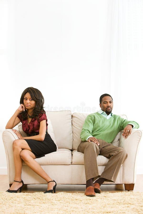 Couples : Homme et femme Sit Apart sur le divan image stock