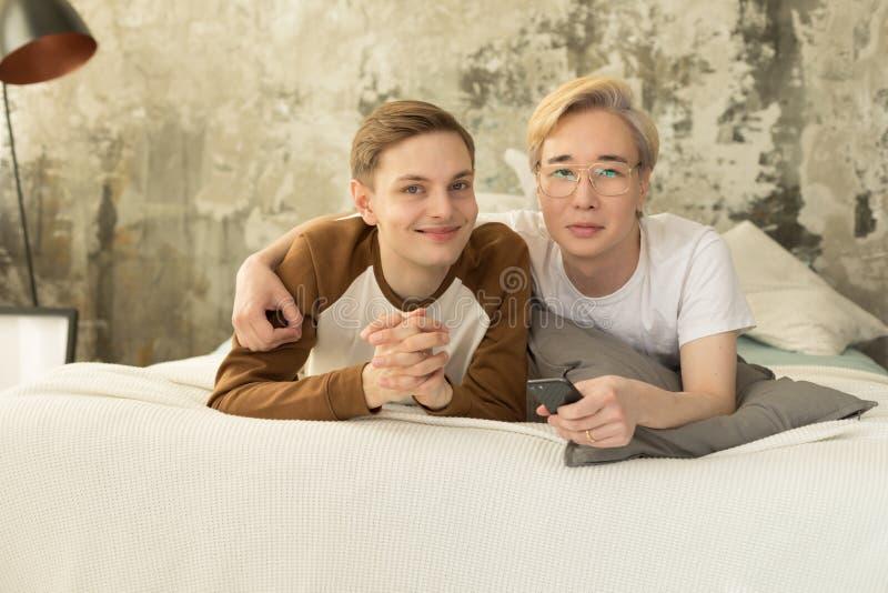 Couples homosexuels internationaux attrayants détendant dans le lit avant sommeil de nuit et regardant la caméra photo stock