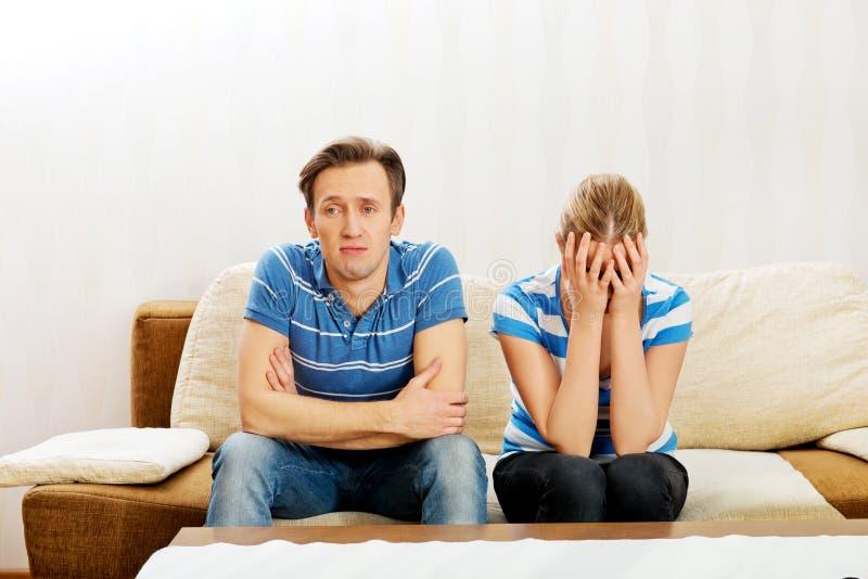 Couples inquiétés après le combat se reposant sur le sofa images libres de droits