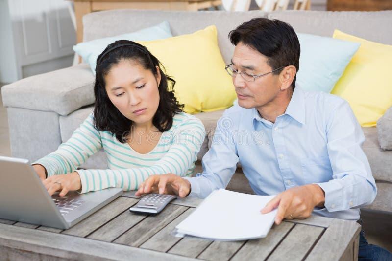 Couples inquiétés vérifiant des factures photo stock