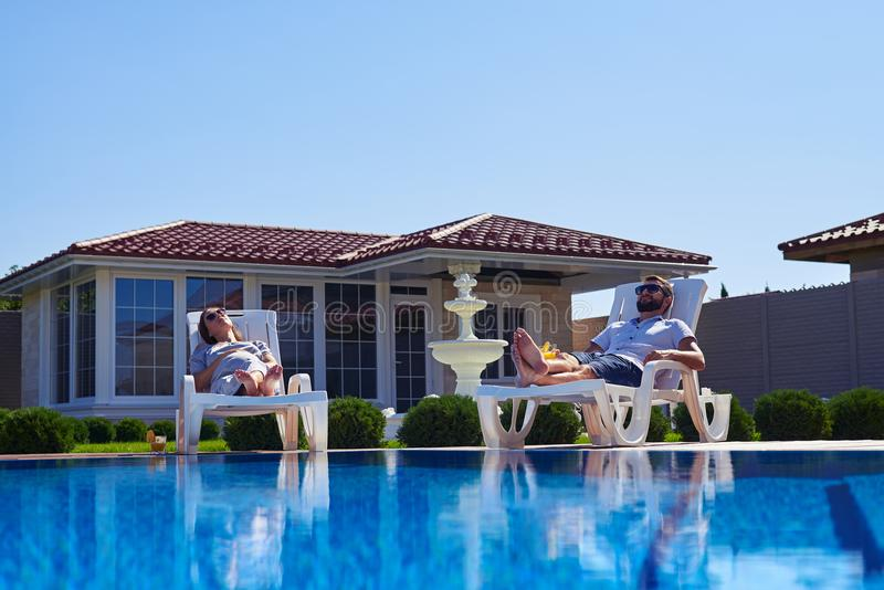 Couples insouciants obtenant bronzages sous le soleil près de la piscine image libre de droits