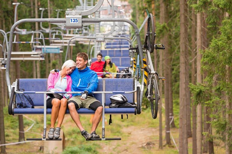 Couples insouciants voyageant par le bois d'ascenseur de chaise photographie stock