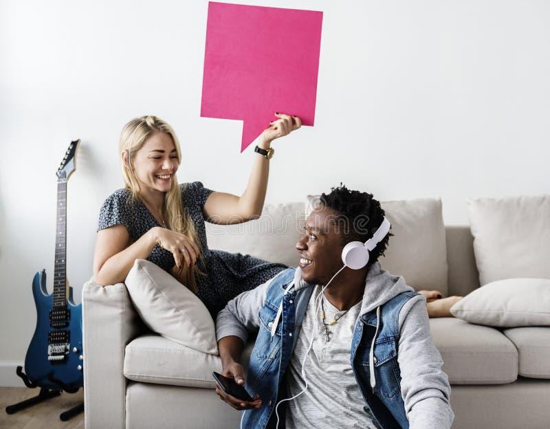 Couples interraciaux partageant la musique à la maison tenant la bulle de la parole de copyspace photo libre de droits