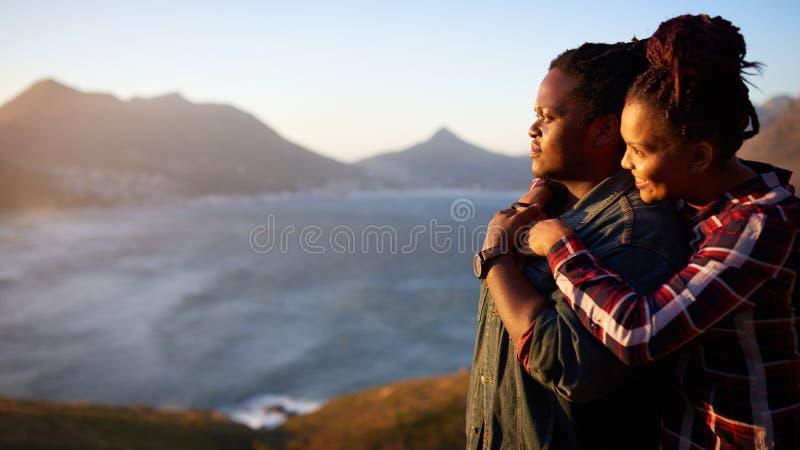 Couples interraciaux regardant l'océan de coucher du soleil et le Mountain View photos stock